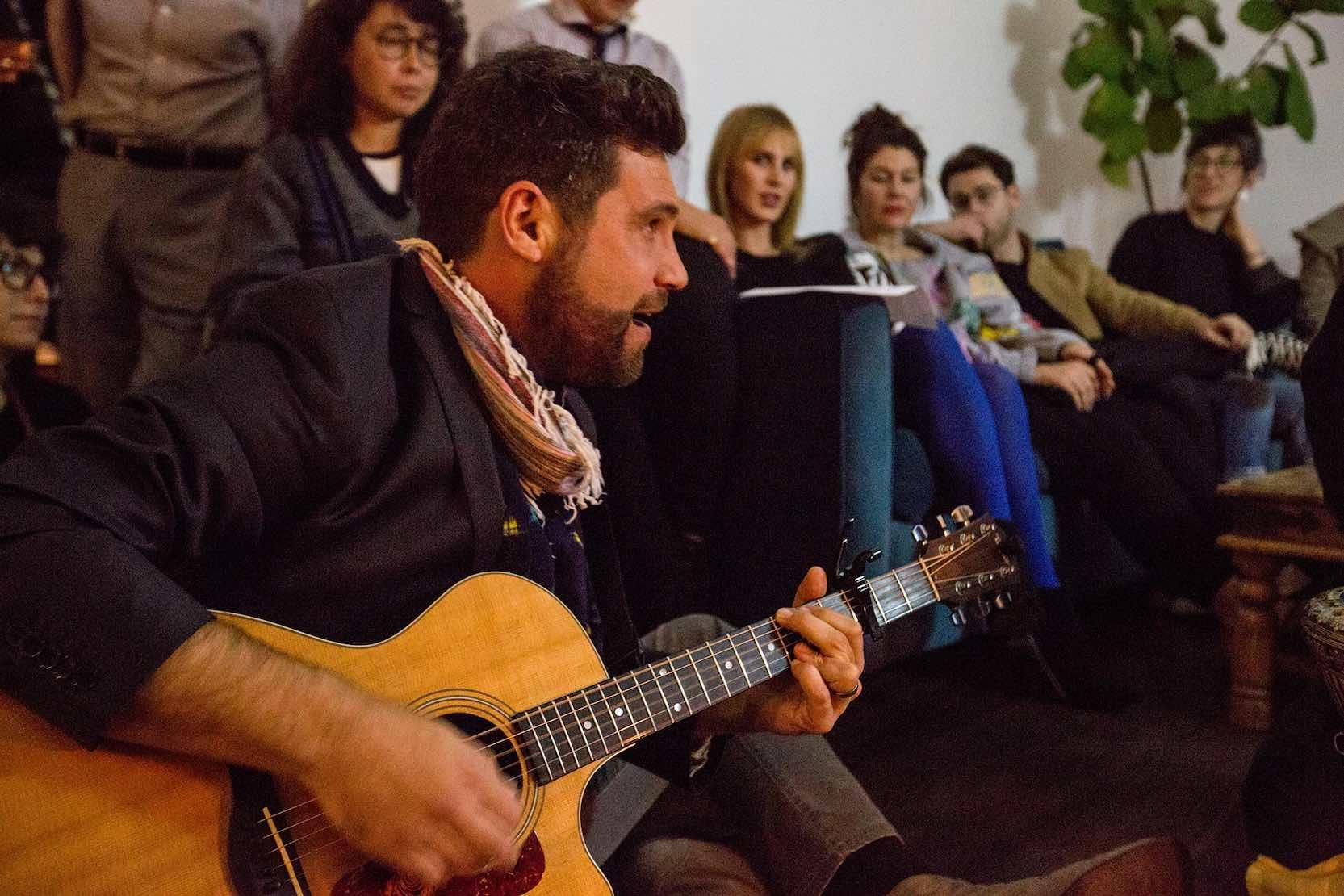 Man plays guitar and sings.