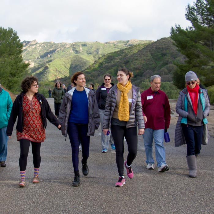 A groupd of people walking with pretty hills in the background.